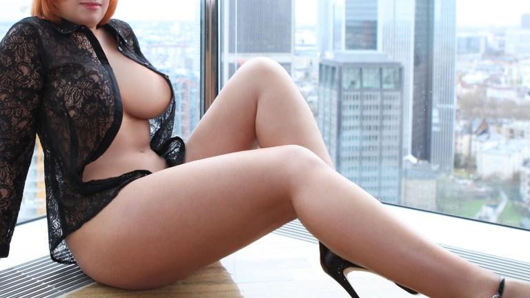 Sofia VIP Escort Independent mit dicken Titten und nackt in einer durchsichtigen Bluse am Fenster sitzend