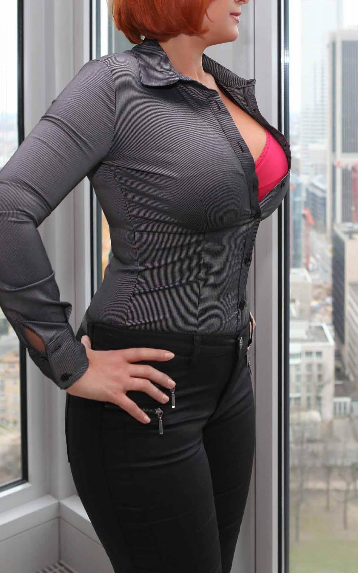 Sofia Begleitdame für VIP Genlemen im sexy Look mit großer Oberweite in einem roten BH in weit geöffnetem Dekolleté als Geschäftsfrau in ihnem Büro