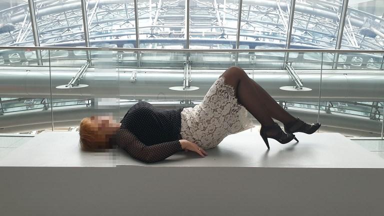 Dipl.-Ing. Sofia und Escortservice in Hilton Frankfurt Airport Hotel liegend auf dem Podest vor dem Panoramafenster