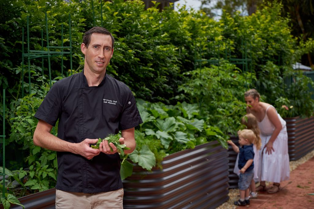 Josh holding his herbs in the herb garden with family in the background