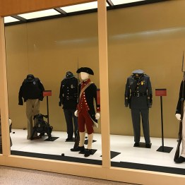 Exhibit showcase overview with past uniforms in the front and modern ones behind