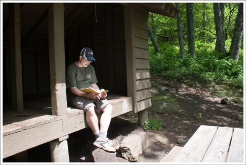Adam enjoys reading the journal at the AT shelter.