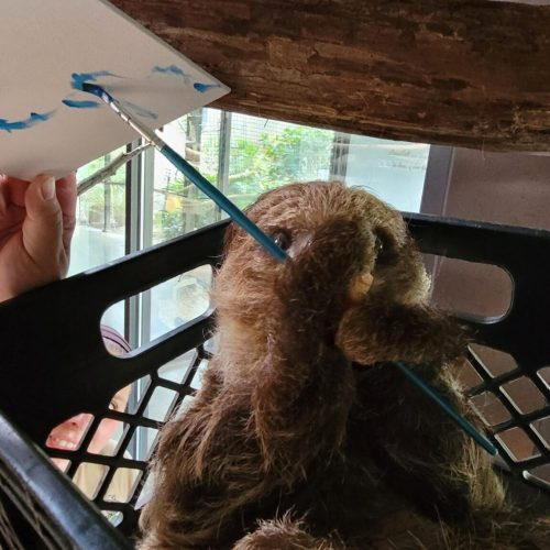 sloth using paintbrush to paint on canvas