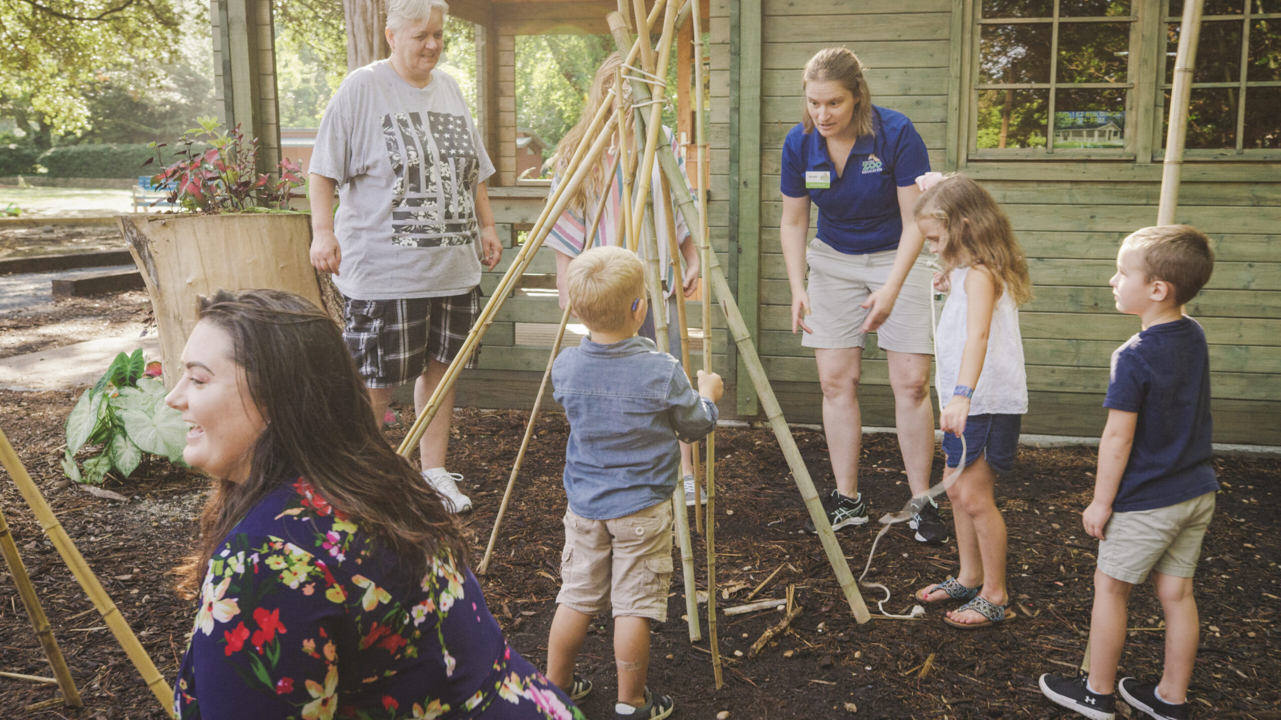 Children and adults gather to build a teepee