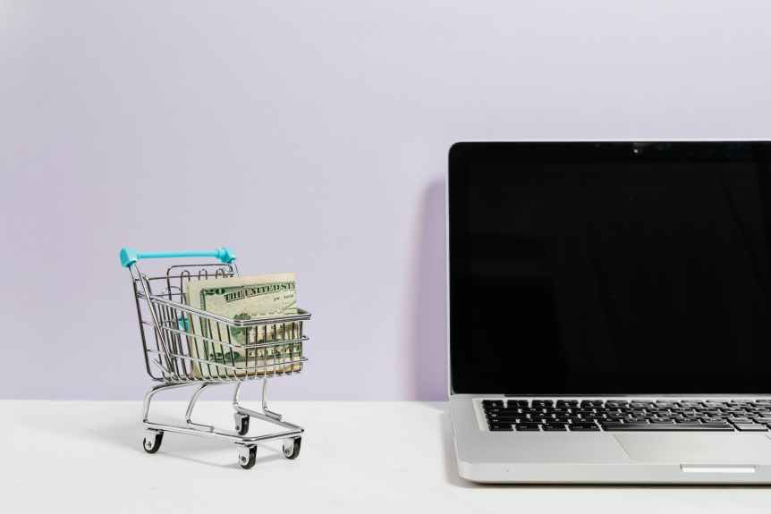 macbook pro on white table beside a miniature shopping cart with money