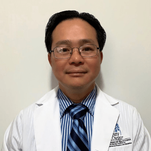 Asian male doctor with a lab coat and tie.