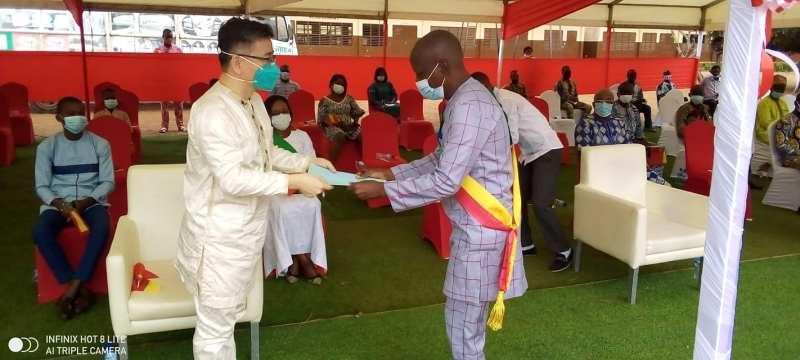 Le Maire Joseph Hounkanrin de la Commune d'AKpro-Missérété ( à droite) recevant des mains de Peng Jing Tao, ambassadeur de Chine près le Bénin, les actes du Projet «Accès à la télévision par satellite »