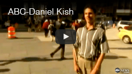 Image: Video still shows Daniel Kish standing at a street corner with people walking in the background.