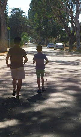 IMAGE: Daniel Kish instructs 9 year-old Nava Madani in FlashSonar echolocation and full-length cane technique along a tree-lined street.