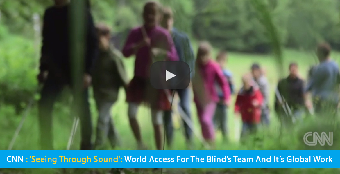Large Video Thumbnail shows children and young teens walking from a field into a forest in Germany in a workshop by World Access For The Blind. Text band reads: CNN: 'Seeing Through SOund': World Access For he Blind's Team and it's global work. Click on the thumbnail to watch the video at CNN.