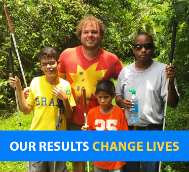 Our results change lives. Photo: Brian Bushway stands with 3 young students in Belize.