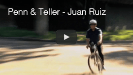 Video thumbnail from Penn and Teller-Juan Ruiz shows Juan wearing a helmet while riding his mountain bike on a street. CLick on the thumbnail to go to the video.