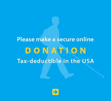 Please make a secure online donation. Tax deductible in the USA. Click on the box to go to our donation page. Image shows a light blue silhouette of Daniel Kish walking with a full-length cane against a deeper blue background.