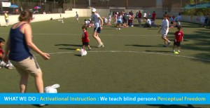 Page banner shows a soccer clinic inside a walled-in outdoor soccer and field hockey field. Blind children and teens are learning soccer shill using soccer balls wrapped in plastic bags for audability. The text band reads: What We Do: Activational Navigation: We teach blind persons Perceptual Freedom.