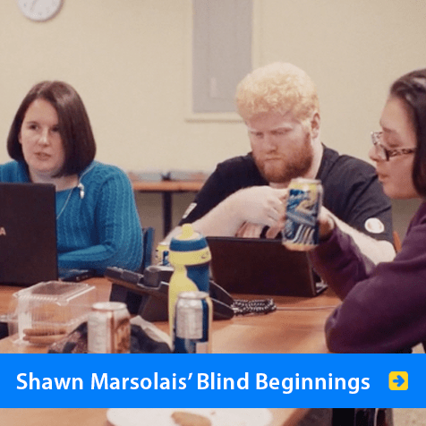 Shawn Marsolais' Blind Beginnings. Image of Shawn Marsolais in discussion with students around a conference table at Blind Beginnings's youth leadership group.