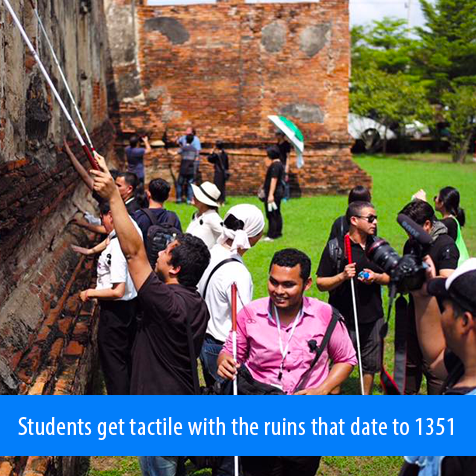 Students get tactile with the ruins that date to 1351. Image. Students raise their canes high against the decaying brick walls of the ruins under the supervision of Brian Bushway and Juan Ruiz.