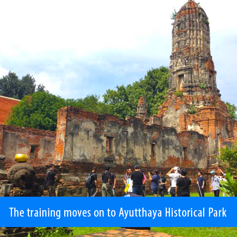 The training moves on to Ayutthaya Historical Park. Image shows instructors and students standing next to a wall of the ruins.