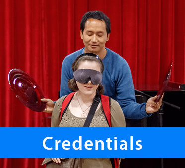 Credentials. Photo: Thomas Tajo stands behind a seated , blindfolded woman holding a large plate to each side of her as part of a FlashSonar demonstration.