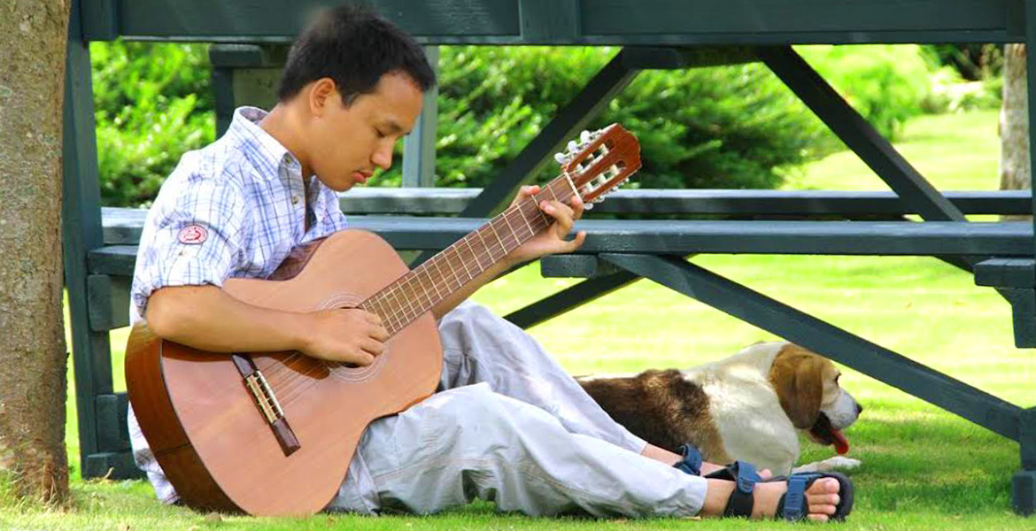 Photo: Thomas Tajo sits on the grass next to a park table and plays guitar . His dog sits on the grass behind him.