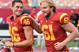 Photo of Jake Olson, 18 year-old long snapper for the USC Trojans runs with his hand on the shoulder of a team mate after snapping for the winning point in a game.