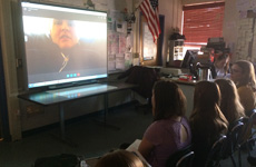 Visioneer J. Steel-Louchart is pictured on a large video screen interacting with a Science class of students via Skype.