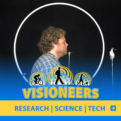 Category link: Research, Science and Tech. Visioneer Brian Bushway is pictured standing next to circular tubing and a microphone during research testing in the U.K.