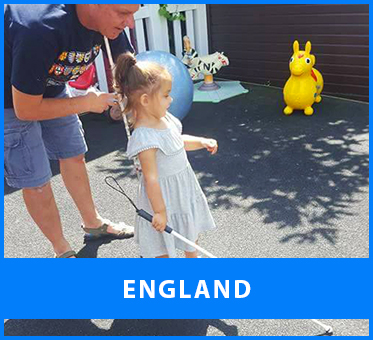 England. Image: Lead Visioneer Daniel Kish bends over as he instructs a young blind girl on using her long Perception Navigation Cane on the patio in her back yard on a sunny day.