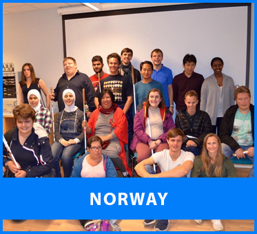Norway. Image: Lead Visioneer Daniel Kish stands beside Workshop Visioneer Thomas Tajo in a group photo with blind students in Norway at a weekend workshop.