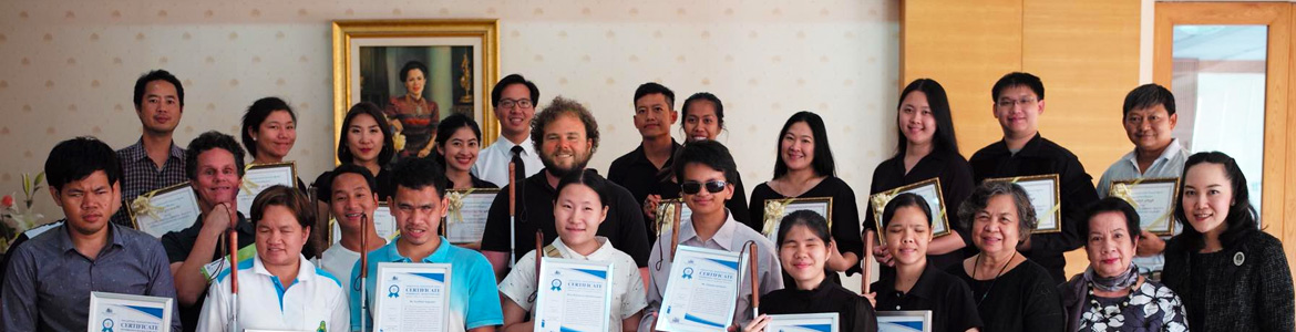Image: Lead Visioneer Daniel Kish, Senior Visioneer Brian Bushway and Workshop Visioneer Thomas Tajo stand for a group photo with staff and blind coaching students at the Foundation for the Blind in Thailand. The student coaches are holding their framed Instructor Level Certificates.