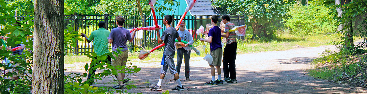 Image: Student Visioneers joust with long pool floats covered with plastic bags at each end in the woods during an Activational Visioneering Workshop.