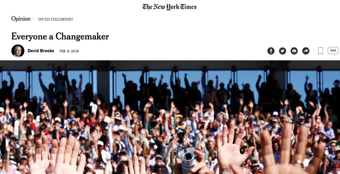 Image: Photo of New York Times online Op-ED section. Opinion | Op-Ed Columnist. Everyone a Changemaker, David Brooks February 8, 2018. Photo of people in a sports stadium with their hands raised high. Credit: Damon Winter/The New York Times.