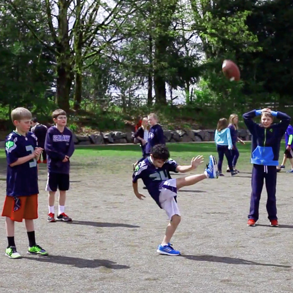 Image: Great video still from Heraldnet.com in 2014 shows Humoody punting a football into the air with his left leg fully extended as his teammates look on.