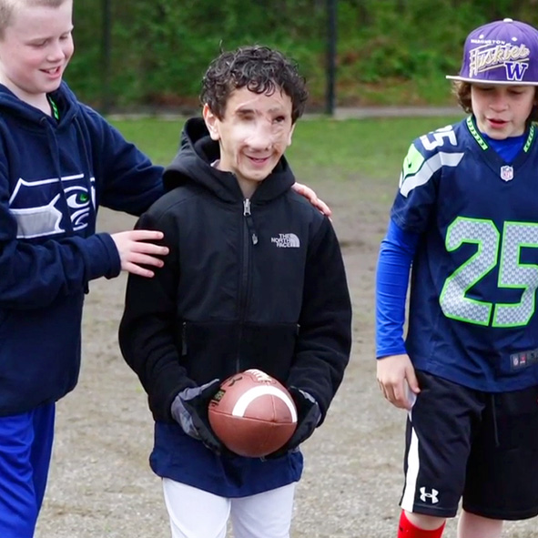 Image: Video still frame from 2014 shows an 11 year-old Humoody Smith holding a football in between two of his teammates as one of them guides him by the shoulders into the direction the ball needs to go.