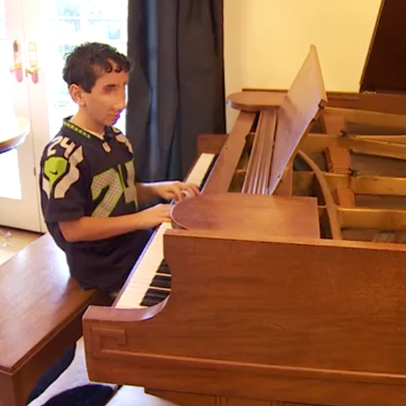 Image: Humoody Smith, wearing his Seattle Seahawks football jersey, sits on a bench playing the piano.