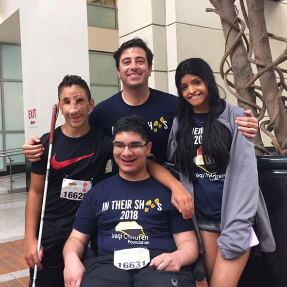 "Photo: Chairman of the Iraqi Children Foundation, Mo Khudairi embraces ICF Youth Ambassadors Humoody , Teeba and Ala'a at the celebration following the 2018 ""In Their Shoes"" 5K fundraiser."