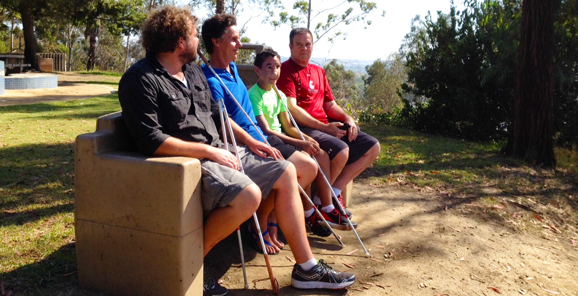 Image: photo of Brian Bushway, Daniel Kish, Humoody Smith and Randy Smith sitting on a park bench overlooking Culver City, California on a sunny day.
