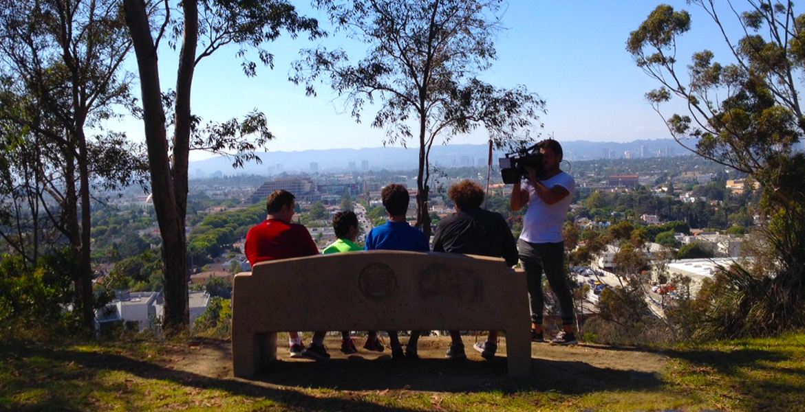 Image: Rear-view of Brian Bushway, Daniel Kish, Humoody Smith and Randy smith sitting on a park bench overlooking Culver City California as a videographer from Nine News Australia shoots video from the front of them.