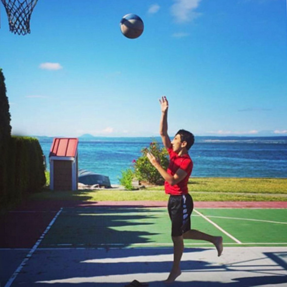 Student Visioneer Humoody Smith is captured floating in air as the camera catches him in the middle of a basketball toss in a yard looking out to Puget Sound in Washington State.