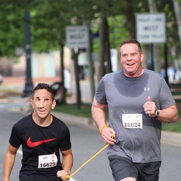"Photo: Humoody and his Dad Randy are tethered together for the 2018 ""In Their Shoes"" 5K event to benefit the Iraqi Children Foundation."