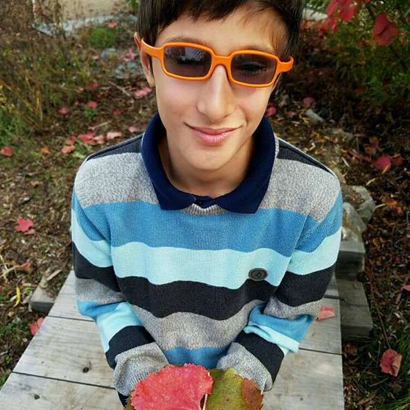 Image: Photo portrait of Student Visioneer Nava wearing orange rimmed sunglasses and holding a colorful leaf in his hands.