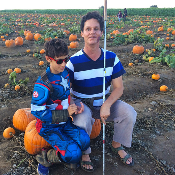 Image: Lead Visioneer Daniel Kish sits with student Visioneer Nava on a pumpkin in the middle of a California pumpkin field. Daniel is holding his full-length Perception Cane while Nava is wearing a Captain America costume for Halloween.