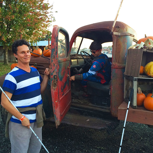 Image: Photo of Lead Visioneer Daniel Kish holding open the Driver's side door of a vintage flatbed pickup truck loaded with pumpkins while Student Visioneer Nava tries out the steering wheel dressed in his Captain America Halloween costume.