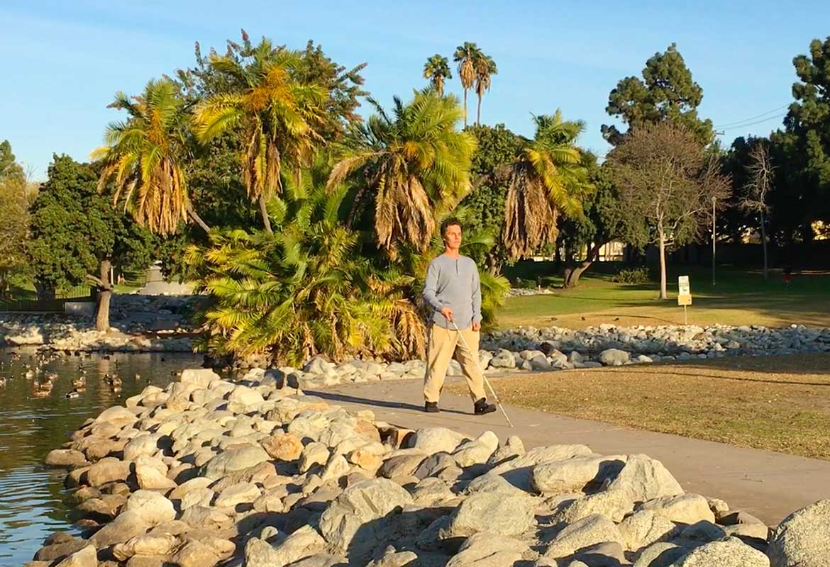 Daniel Kish walks along a curved sidewalk next to a duck pond in a Long Beach, California park using SonarVision and a lightweight Perception Cane.