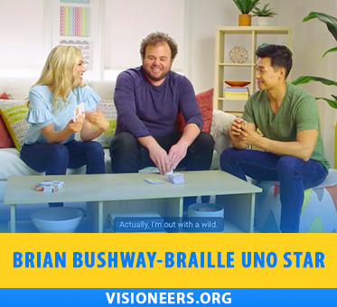 "Brian Bushway - Braille UNO star. Video still frame shows Senior Instructor Visioneer Brian Bushway sitting between two sighted UNO players in a ""How-to"" video for the game."