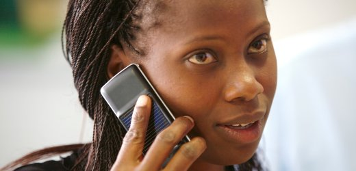 Safaricom Nutzerin client uses a solar-charged mobile phone handset at a retail centre in Kenya's capital Nairobi