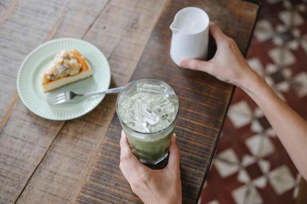 crop unrecognizable woman preparing matcha latte