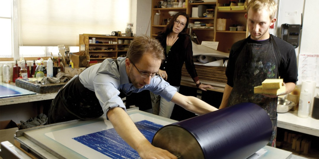 man rolling screen print with blue ink