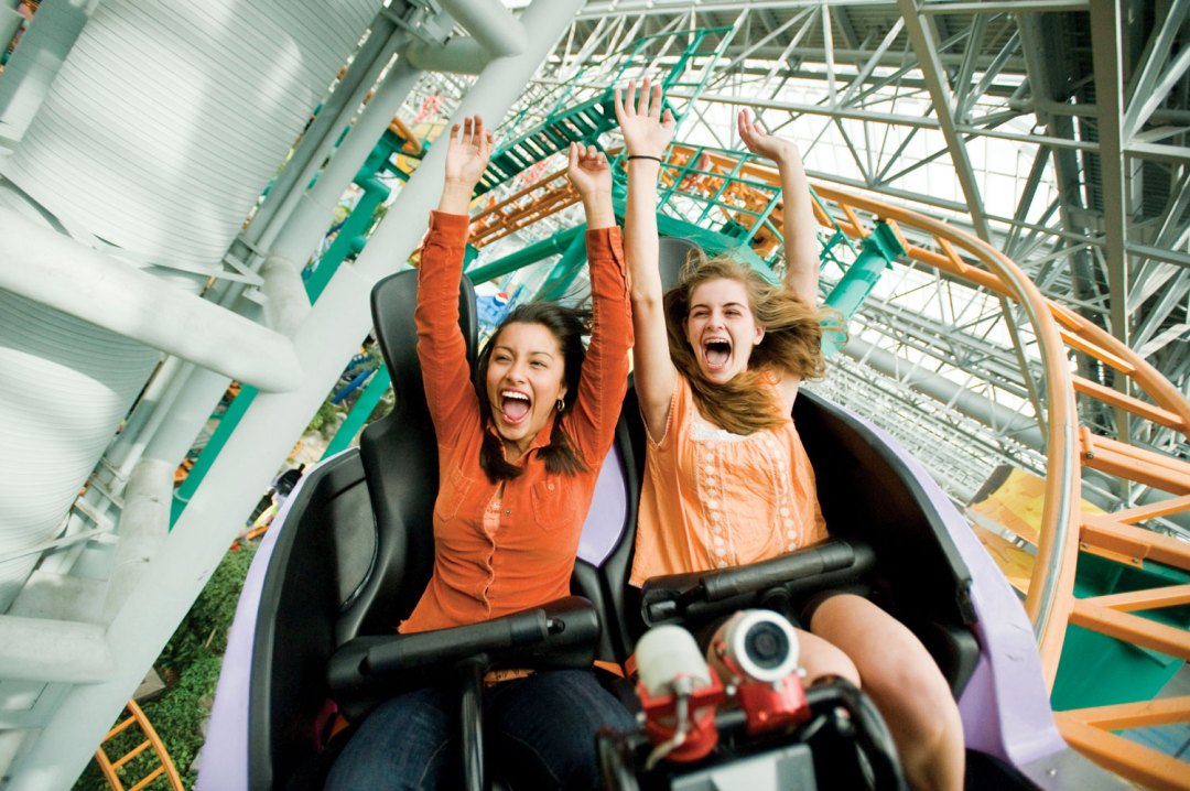 Two girls are riding the Fairly Odd Coaster. Both have their arms in the air and are laughing and smiling.