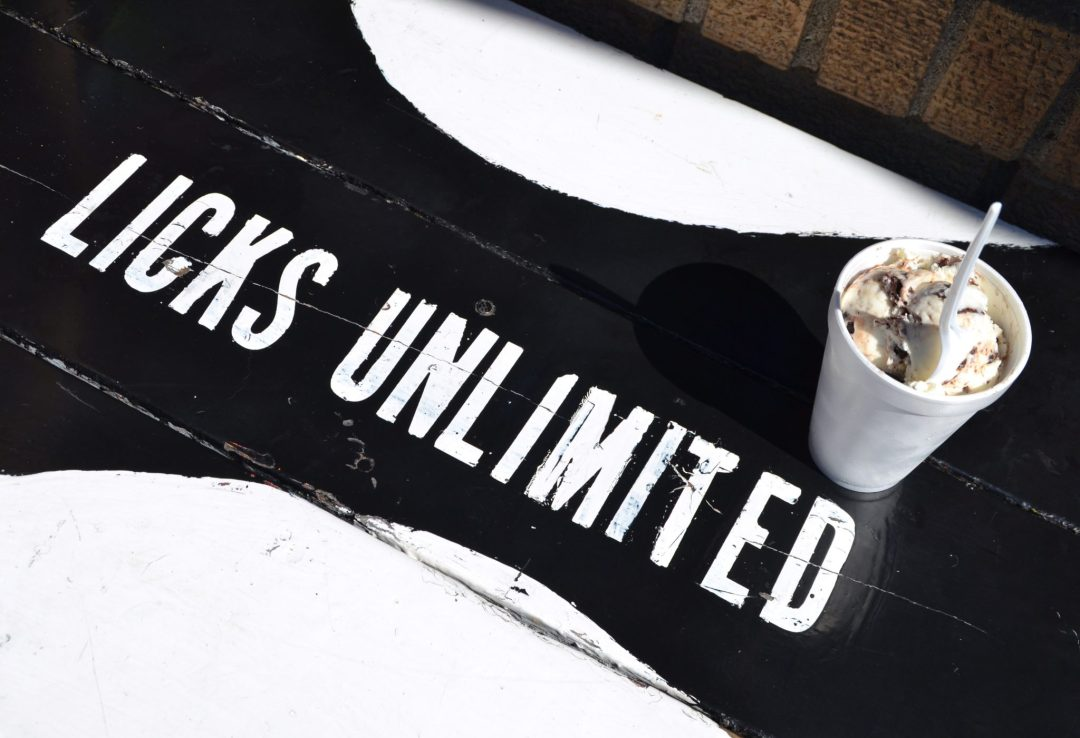 A styrofoam cup filled with ice cream sitting on a table with a black and white Licks Unlimited logo painted on it.