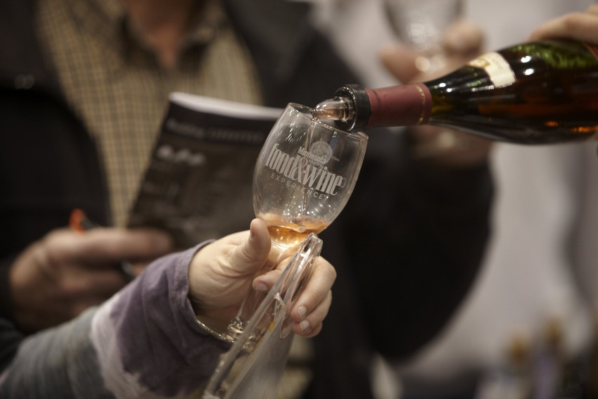 Patrons taste wine at the Food and Wine Experience Photo by Todd Buchanan/Greenspring Media